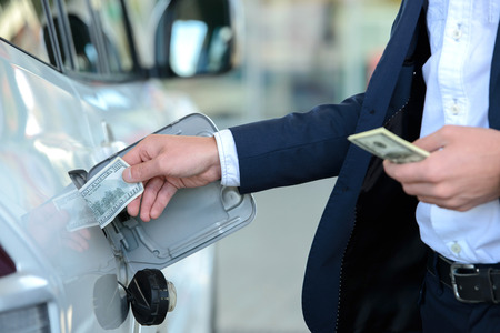 gasoil: Hand of businessman that puts money into the tank of his car instead of gasoline at filling stations. Concept of expensive fuel