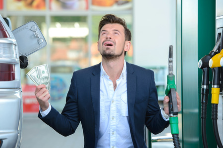 refueling: Emotional businessman counting money with gasoline refueling car at fuel station