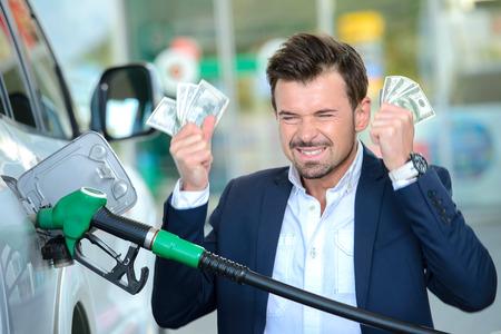 ガソリン給油ガソリン スタンドで車にお金を数える感情的なビジネスマン 写真素材