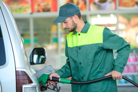 Smiling worker at the gas station, while filling a car