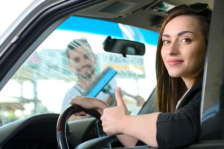 Femme dans la voiture. Lavage fenêtre de la voiture tout en remplissant les voitures à essence à la station service Banque d'images - 31991808