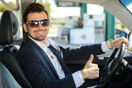 그의 차에 남자가 주유소에서 정차합니다. 스톡 콘텐츠