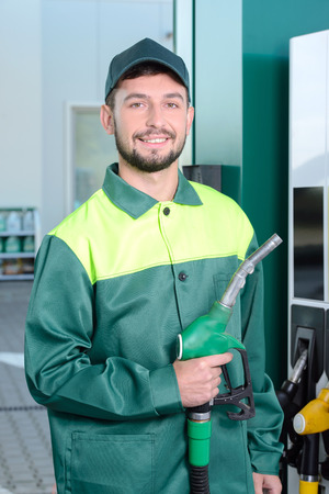 normal distribution: Smiling worker at the gas station, while filling a car