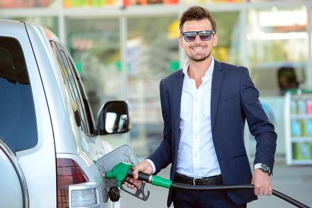 Jeune réservoir de voiture d'affaires de ravitaillement à la station de carburant Banque d'images - 31991825