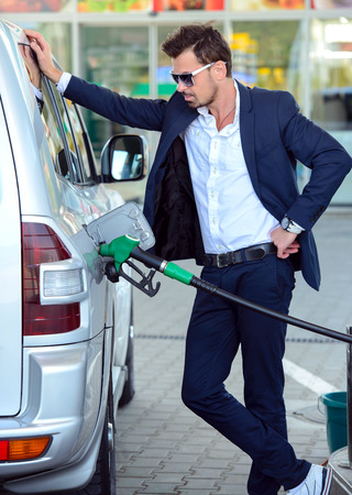 petrol station: Young businessman refueling car tank at fuel station