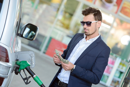 Businessman counting money with gasoline refueling car at fuel station
