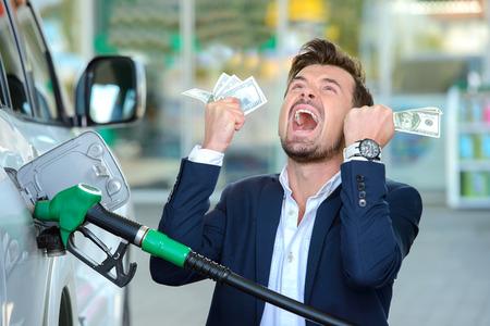pieniądze: Emocjonalne biznesmen liczenie pieniędzy z benzyny tankowania samochodu na stacji paliw