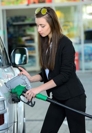 Zakelijke vrouw op het tankstation, tijdens het vullen van uw auto