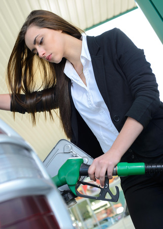 Business woman on filling station, while filling your car