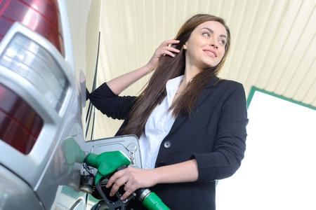 Zakelijke vrouw op het tankstation, tijdens het vullen van uw auto Stockfoto