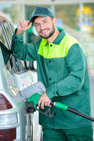 Glimlachende arbeider bij het benzinestation, tijdens het vullen van een auto Stockfoto
