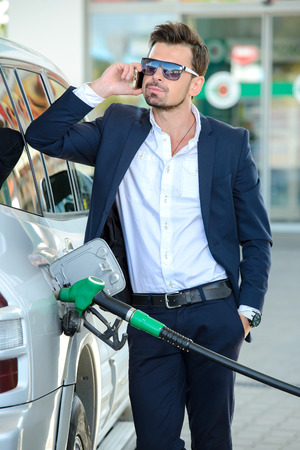 Young businessman refueling car tank at fuel station photo