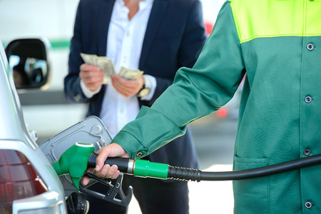 Hombre de negocios da dispensadores de dinero, coche lleno en la gasolinera