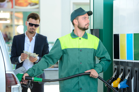 gasoil: Businessman give money dispensers, filled car on gas station Stock Photo