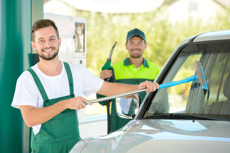 ガソリン スタンドでガソリン車を充填しながら車の窓を洗浄