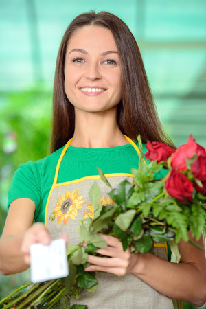 Florist with a bunch of flowers and a business card left blank for your message photo