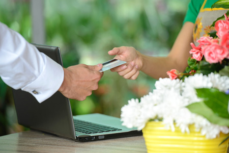 Jonge vrouw die als bloemist werkt die creditcard geeft aan klant na aankoop. Stockfoto