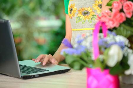 petites fleurs: Portrait d'un propri�taire attrayant fleuriste femme d'affaires assis � un comptoir de magasin de fleurs � l'aide d'un ordinateur portable de placer un ordre d'achat d'actions en ligne. Technologie des petites entreprises.