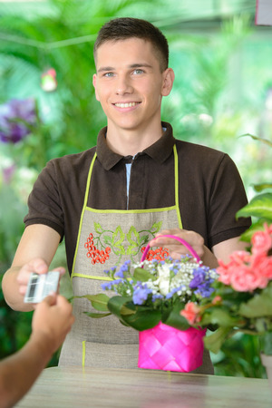 Young man working as florist giving credit card to customer after purchase. photo