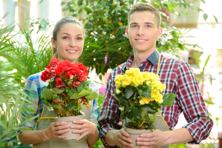 Young smiling florists man and woman working in the greenhouse. photo