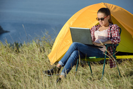 Portrait of succesful woman with laptop sitting in folding chair near camp tent outdoors photo