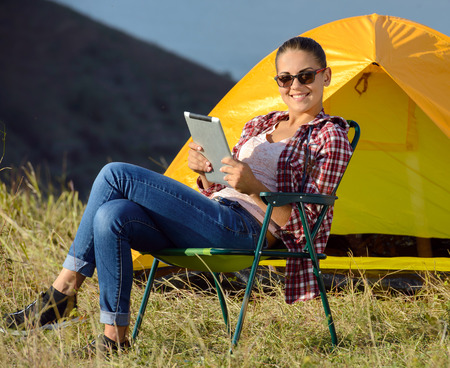 succesful woman: Portrait of succesful woman with tablet sitting in folding chair near camp tent outdoors Stock Photo
