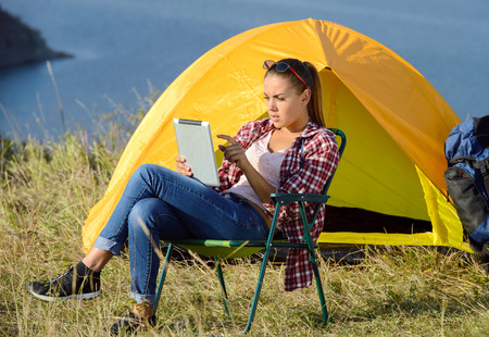 Portrait of succesful woman with tablet sitting in folding chair near camp tent outdoors photo
