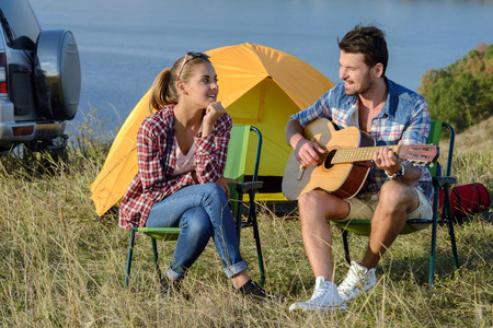 Cute man serenading his girlfriend on camping trip on a sunny day photo
