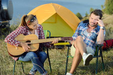 serenading: Cute woman serenading her men on camping trip on a sunny day