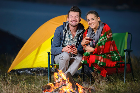 camping tent: Romantic evening. Charming couple near a fire while camping drinking wine