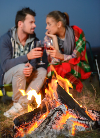 Romantic evening. Charming couple near a fire while camping drinking wine photo