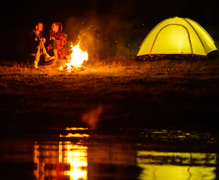 Romantic evening. A charming couple, camping, sitting around the campfire photo