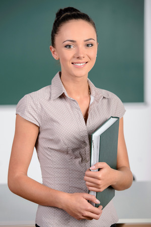 Young smiling student or teacher at the blackboard photo