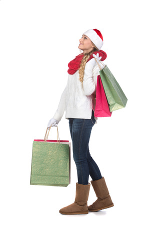 Christmas Shopping. Happy Woman with Shopping Bags in Shopping Mall. Sales. Christmas Gifts. isolated on white background photo