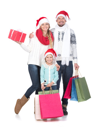 Portrait of young couple and their daughter in Santa caps looking at camera. Isolated on white background. photo