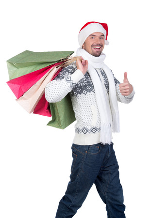 Happy smiling young man in Santa Claus hat with shopping bags, isolated on white background photo