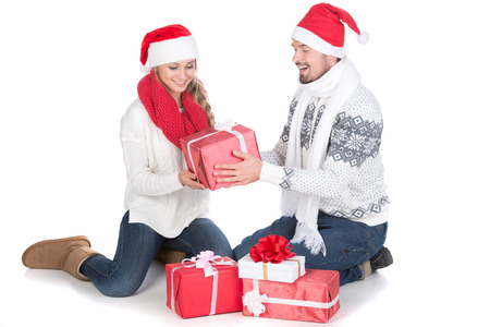Young couple at Christmas with Santa Claus hats. Isolated on white background. photo