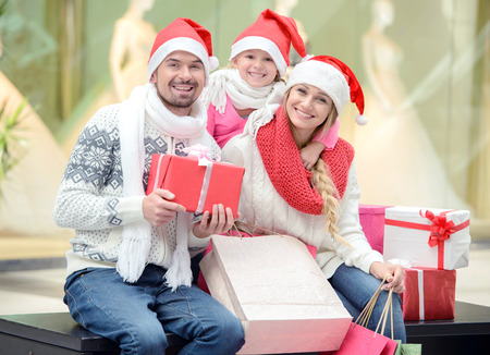 Portrait of young couple and their daughter in Santa caps looking at camera in the mall photo