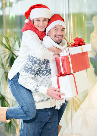 Portrait of happy couple in Santa caps looking at camera in the mall photo