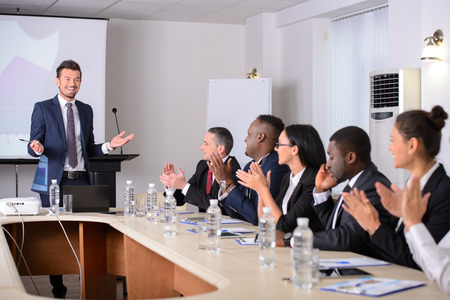 aplaudiendo: Conferencia de negocios. Reuni�n de negocios. Gente de negocios en ropa formal hablando de algo mientras est� sentado junto a la mesa