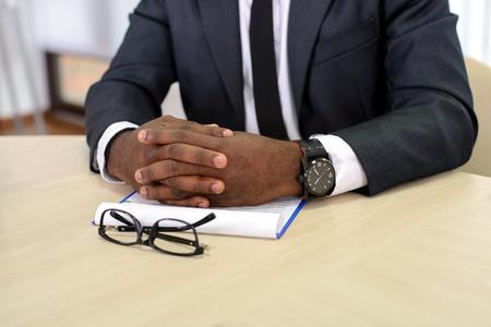 Close-up van een zwarte zakenman die vingers houdt die voor zich worden gekruist Stockfoto