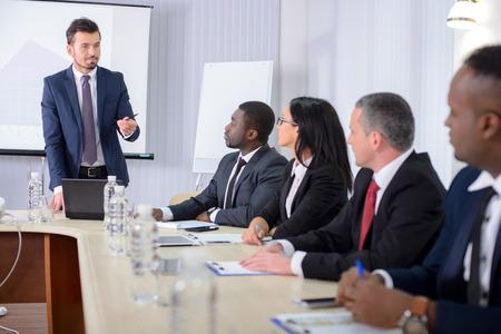 reuniones empresariales: Conferencia de negocios. Reuni�n de negocios. Gente de negocios en ropa formal hablando de algo mientras est� sentado junto a la mesa