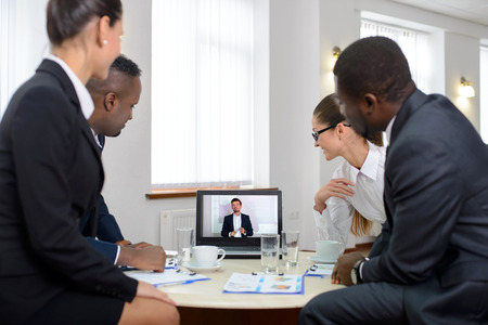 Group of male and female businesspeople seated at a table watching an online conference on a computer screen photo