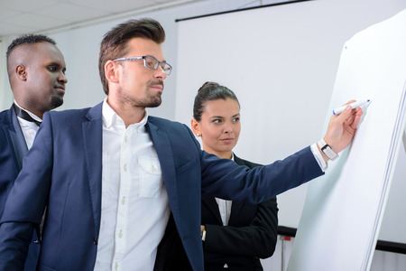 new strategy: Young multiethnic business team planning a new strategy standing grouped in front of a flip chart analyzing a chart