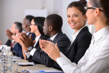 aplaudiendo: Conferencia de negocios. Reunión de negocios. Hombres de negocios en ropa formal hablando de algo mientras está sentado junto a la mesa