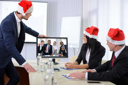 Group of male and female businesspeople seated at a table watching an online conference on a computer screen, during the celebration of Christmas photo