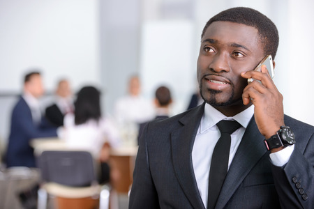 african business: Portrait of black businessman, people group in background at modern bright office indoors Stock Photo