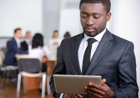 黒の実業家、近代的な明るいオフィス室内でバック グラウンドで人々 のグループの肖像画