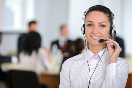 Female customer support operator with headset and smiling, people group in background at modern bright office indoors photo