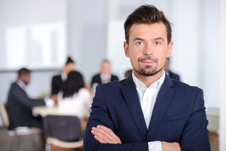 board room: Portrait of a young businessman, people group in background at modern bright office indoors Stock Photo